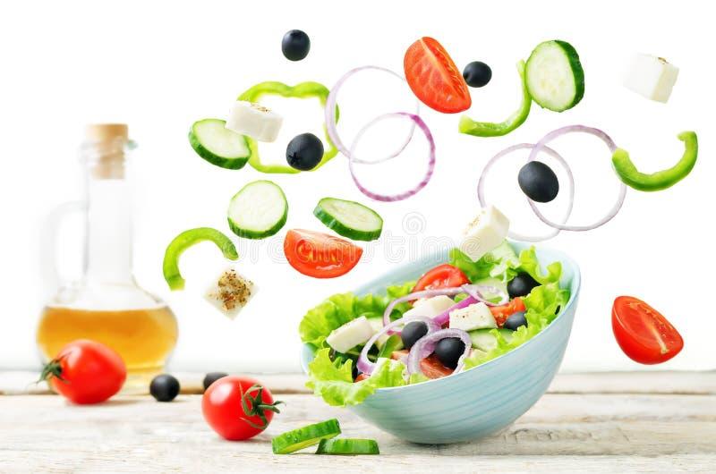 Греческий салат с ингридиентами летания, который нужно подготовить его стоковое изображение rf