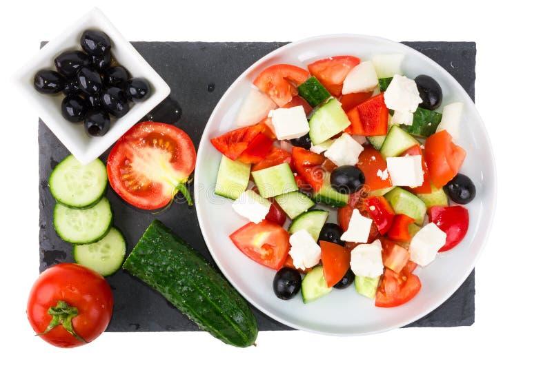 Греческий салат с свежими овощами, сыром фета и черными оливками в плите с ингридиентами на белой предпосылке стоковое изображение
