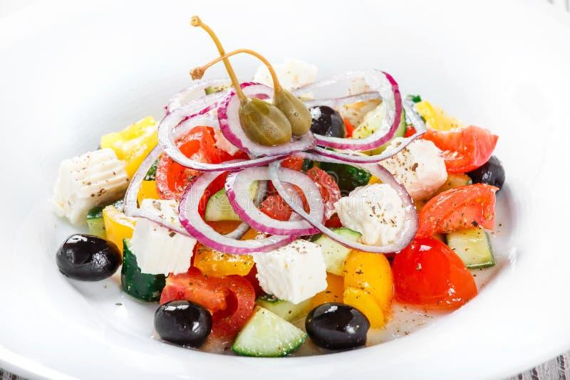 Греческий салат с свежими овощами, оливками и сыром фета на деревянном конце предпосылки вверх стоковая фотография