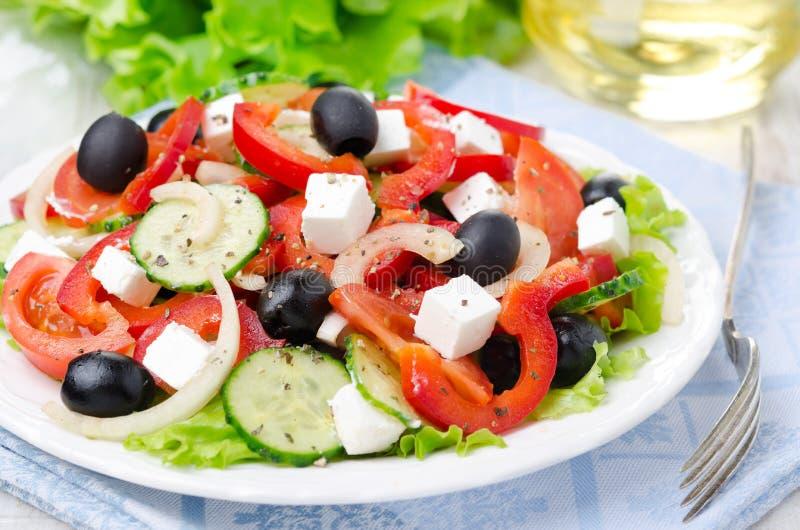 Греческий салат с сыром, оливками и овощами фета на плите стоковые фотографии rf