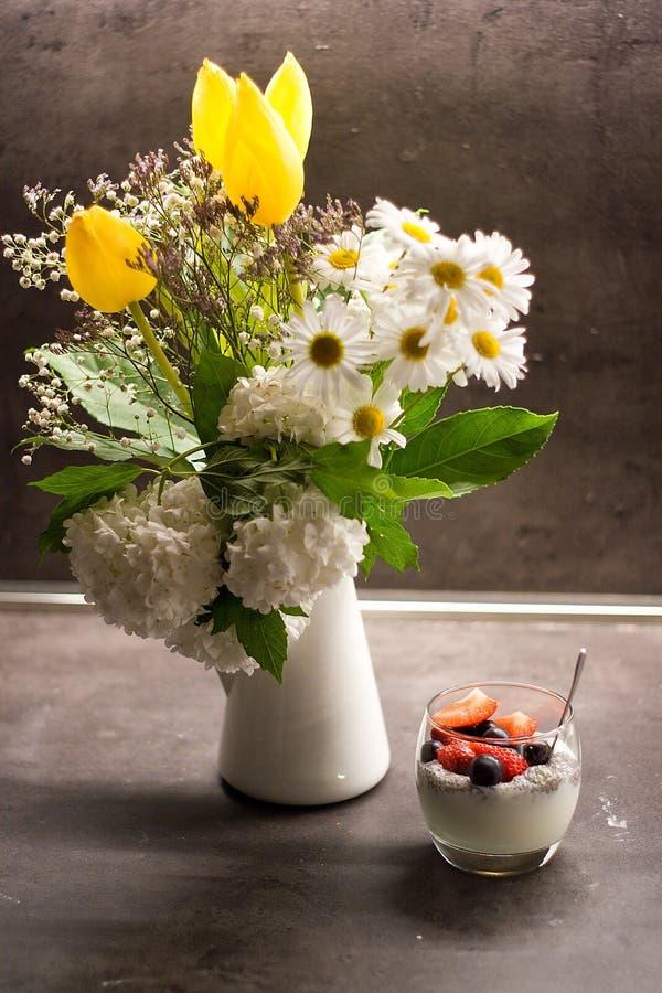 Греческий югурт с семенами chia кокоса и свежими фруктами рядом с цветками в вазе стоковая фотография