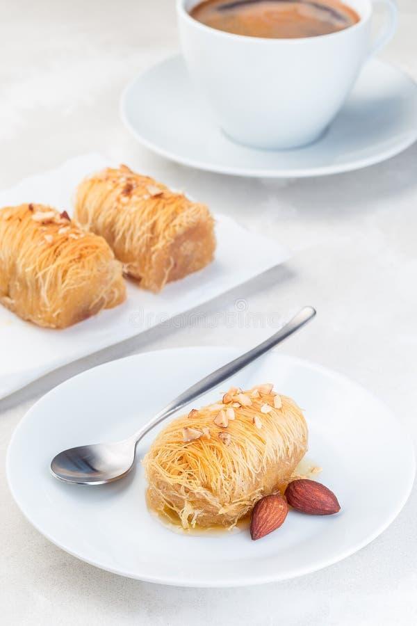 Греческое печенье Kataifi с shredded тестом filo заполненным с гайками миндалины, в сиропе меда, на белой плите, который служат с стоковая фотография