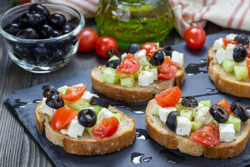 Греческое crostini стиля с сыром фета, томатами, огурцом, оливками, травами стоковая фотография rf