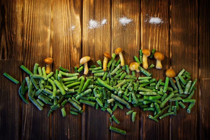 Грибы меда, зеленые фасоли и соль на деревянной предпосылке стоковые изображения