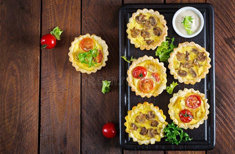 Грибы, чеддер, tartlets томатов на деревянной предпосылке стоковые изображения
