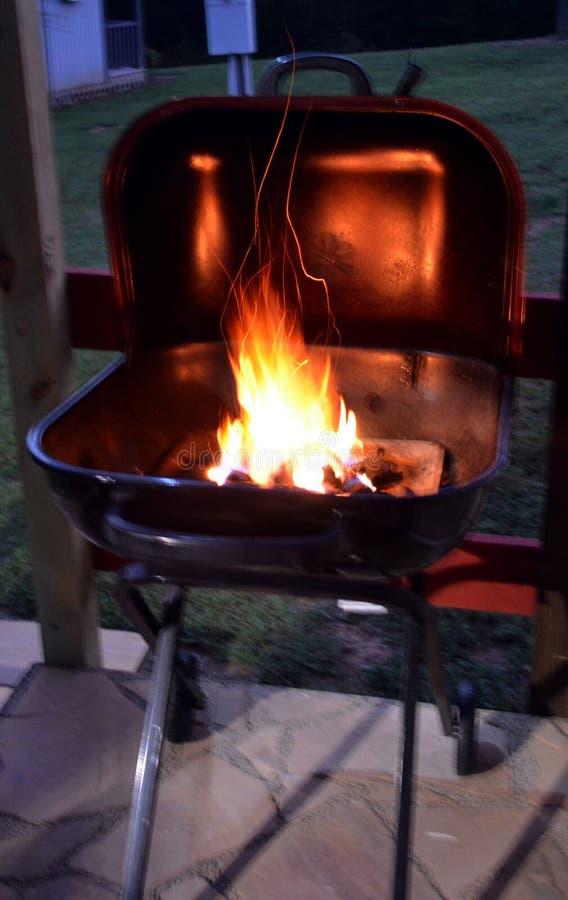 Гриль барбекю с пламенеющими брикетами угля стоковая фотография