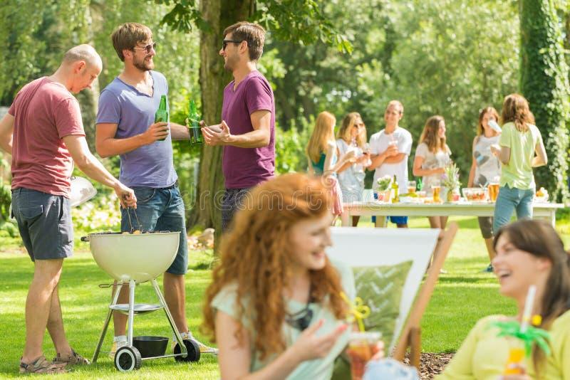 Гриль и смех друзей в парке стоковое фото rf