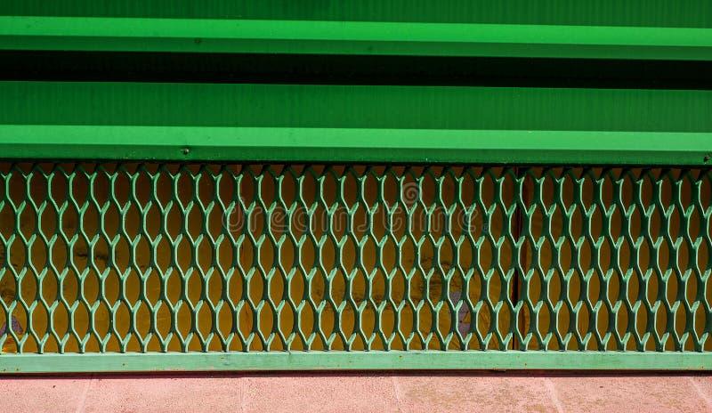 Гриль утюга старый на вниз части двери Геометрические отверстия покрасили зеленым цветом стоковая фотография