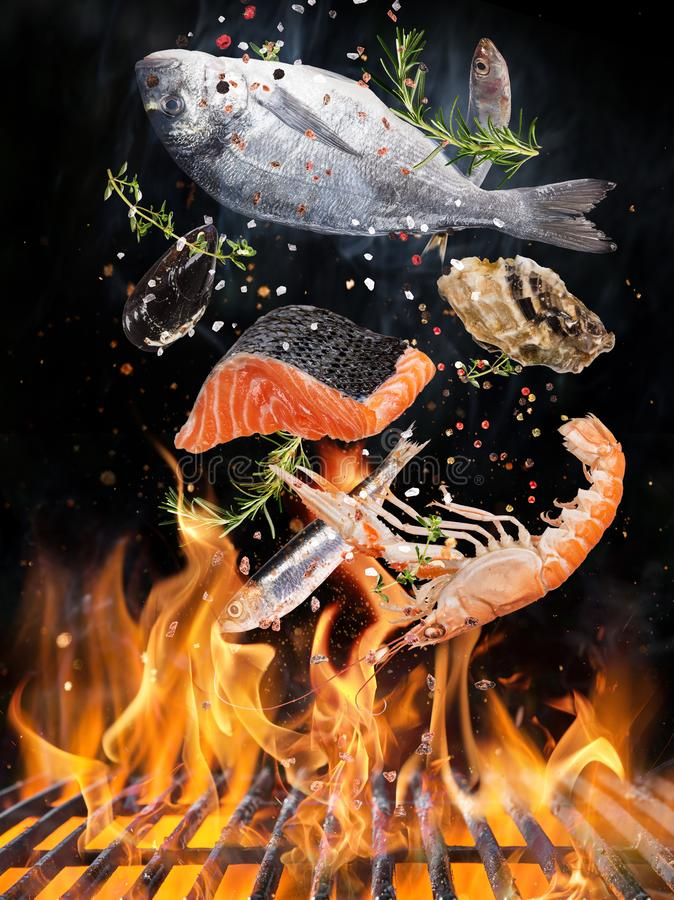 Гриль чайника с пламенами огня, решеткой литого железа и вкусными рыбами моря летая в воздух стоковое фото rf