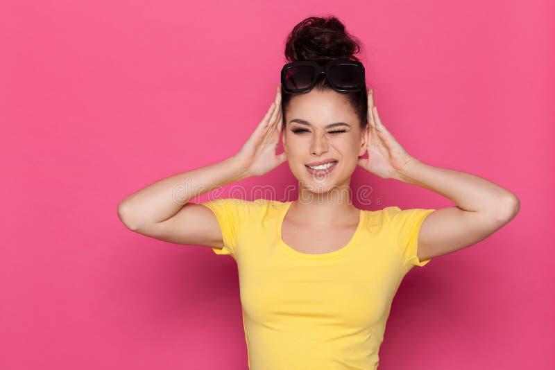 Гримасничая молодая женщина держит головной в руках стоковое изображение rf
