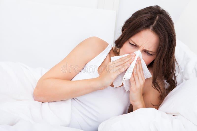 грипп имея детенышей женщины стоковое изображение rf