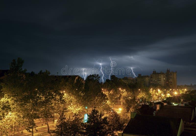 Гроза молнии над городом вечером стоковое фото rf