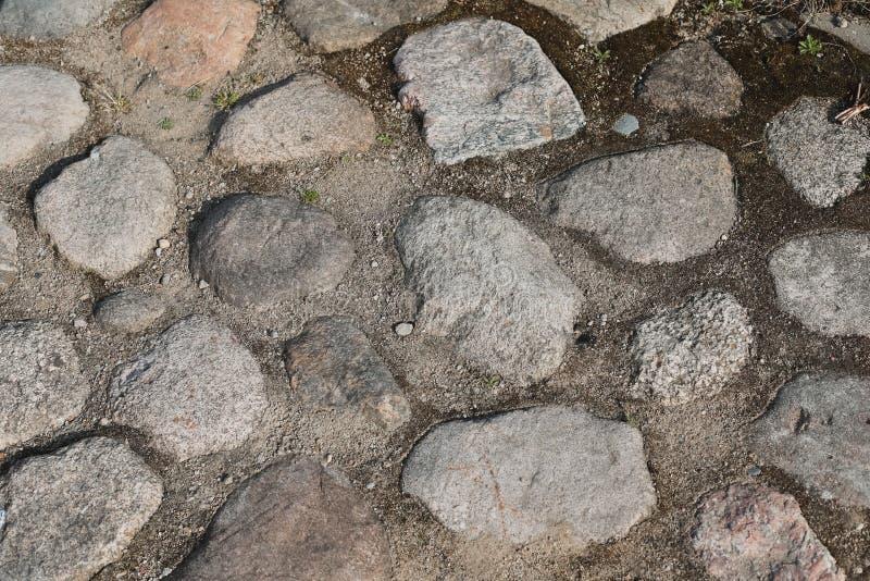 Грубая каменная тропа Старая мостовая сделанная с различными камнями и камешками Предпосылка Grunge каменная Естественный фон гра стоковое изображение