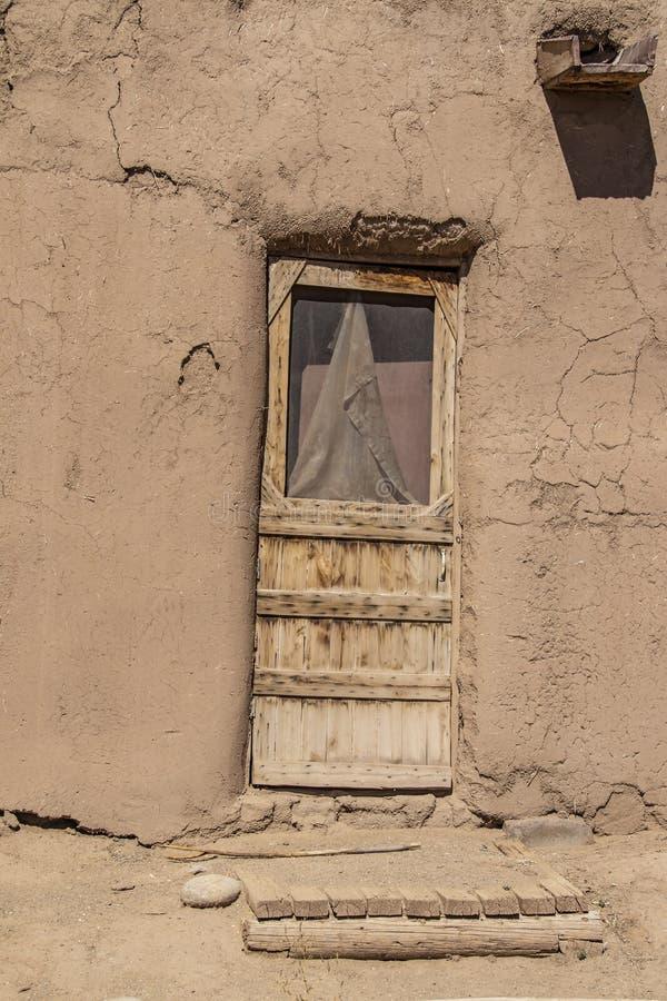 Грубая срубленная деревянная дверь с поврежденным экраном и деревянным крылечком в жилище Пуэбло грязи самана в Taos Неш-Мексико стоковые изображения rf