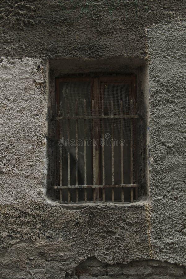 Грубые бары на окне старого дома стоковые изображения