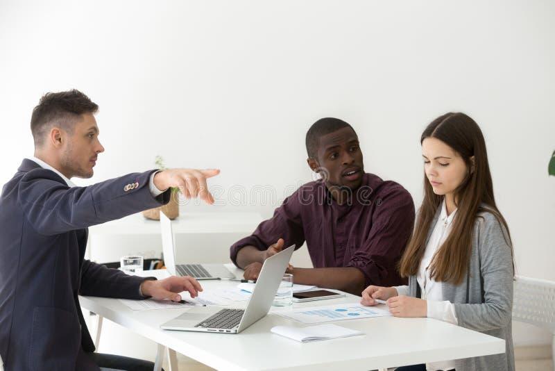 Грубые multiracial бизнесмены унижая увольняющ женский коллега стоковое фото rf