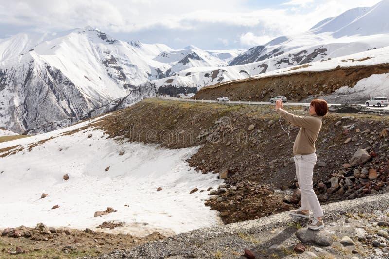Грузинская военная дорога, GE 3-ье мая 2019: Молодая женщина фотографируя возбуждая взгляд Снег-покрытых пиков гор Кавказ стоковое фото rf