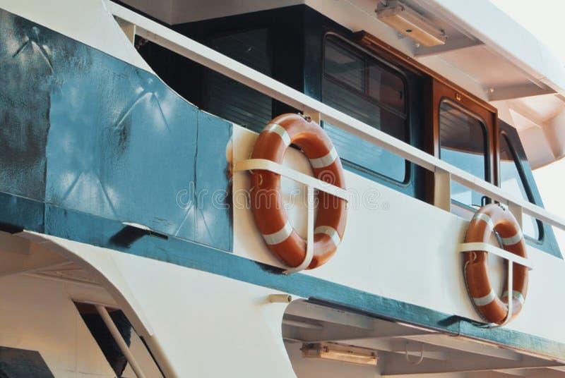 Грузите детали, 2 оранжевых кольца спасателей lifebuoys вися att стоковая фотография rf