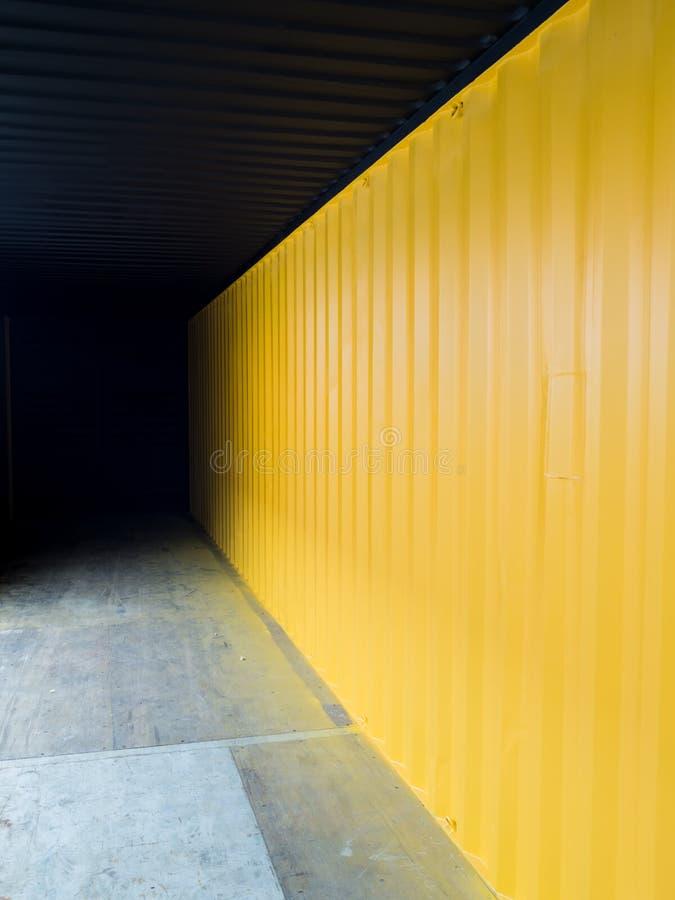 Грузовой контейнер глубоко к темноте с желтой стеной стоковые фотографии rf