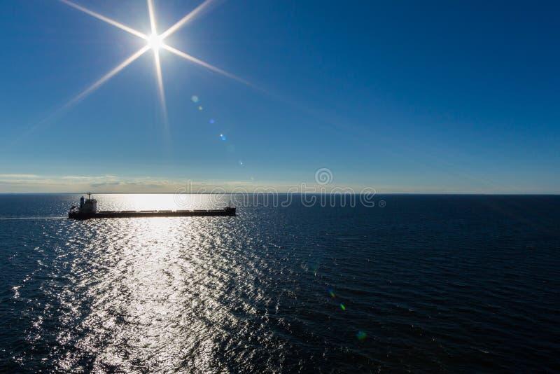 Грузовой корабль в глубоководном синем море и ска с солнечным сиянием стоковое изображение rf