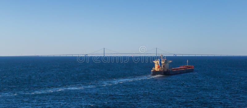 Грузовой корабль в глубоководном синем море с осемандским шумом на горизонте стоковые изображения rf