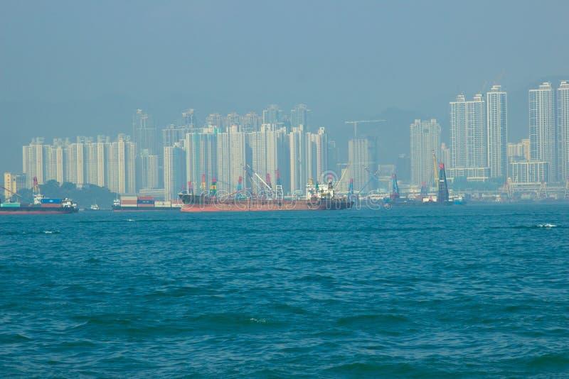Грузовой корабль и промышленные шлюпки плавая в док моря на небоскребах и строя предпосылке Корабль Feight в рекламе стоковые фото