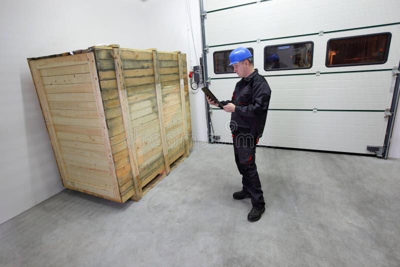 Груз - поставка, работник проверяя большую деревянную коробку с таблеткой стоковое фото