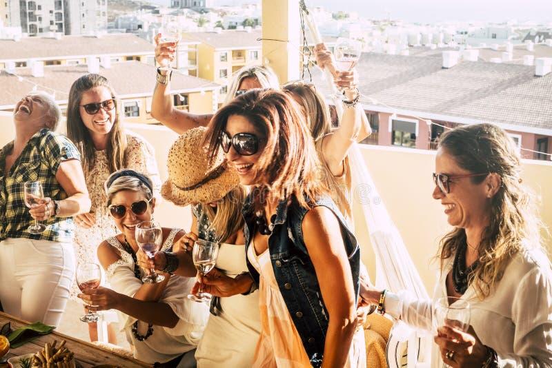 группа веселых людей, молодых и пожилых женщин весело празднуют вместе с вином и весело проводят время на террасе. стоковая фотография rf