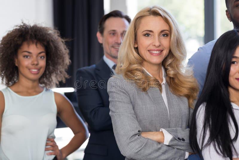 Группа в современном офисе усмехаясь, женский босс предпринимателей коммерсантки ведущая над бизнесменами сложенной стойки команд стоковое фото rf