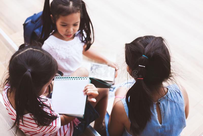 Группа в составе азиатские дети читая книгу стоковое изображение
