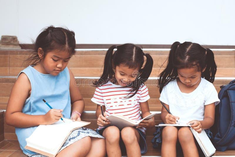 Группа в составе азиатские дети читая книгу стоковые фото