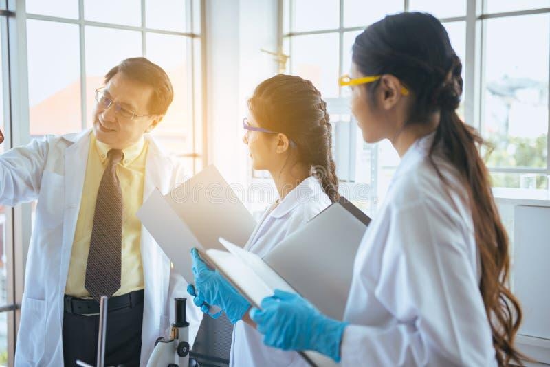Группа в составе азиатские студент-медики исследует новый проект со старшим профессором на лаборатории стоковые фотографии rf