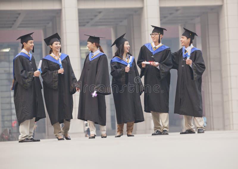 Группа в составе аспиранты в мантиях градации и mortarboards стоя и разговаривая с дипломами в руках стоковое фото rf