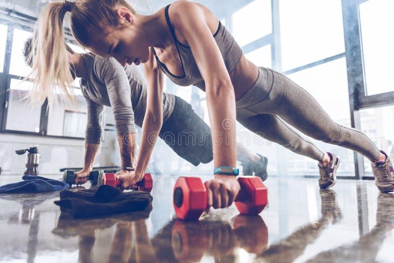Группа в составе атлетическое молодые люди в делать sportswear нажимает поднимает с гантелями на спортзале стоковая фотография