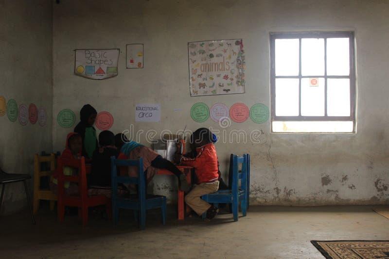 Группа в составе африканские дети изучая столом в сельском Свазиленде стоковые изображения