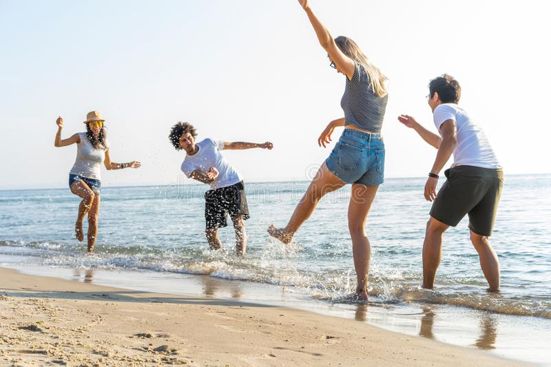 Группа в составе бег друзей через волны совместно на каникулах пляжа стоковое фото rf