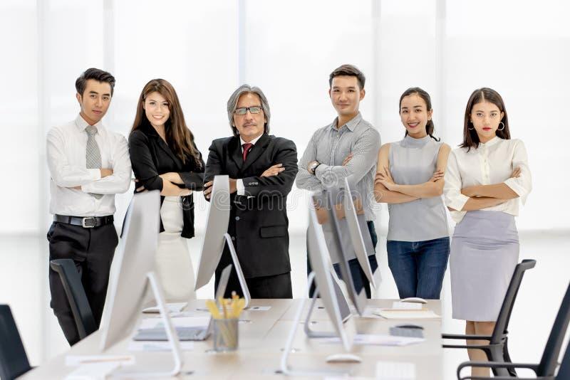 Группа в составе 6 бизнесменов Asaina стоя совместно в современном  стоковая фотография