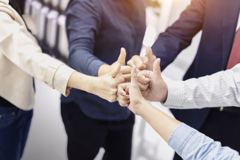 Группа в составе бизнесмены давая большим пальцам руки вверх по жесту утверждения успех, ютится совместно, показывающ единство и  стоковая фотография rf