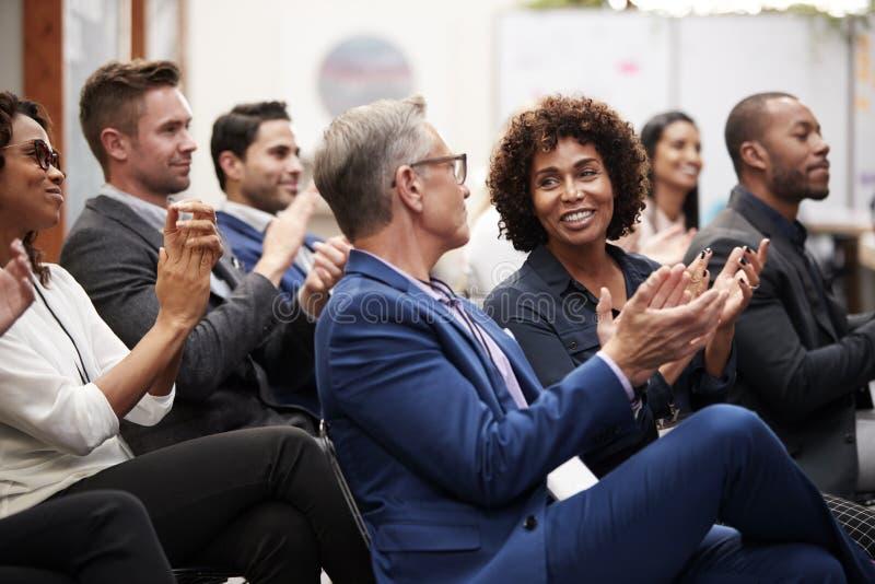Группа в составе бизнесмены и коммерсантки аплодируя представлению на конференции стоковое изображение