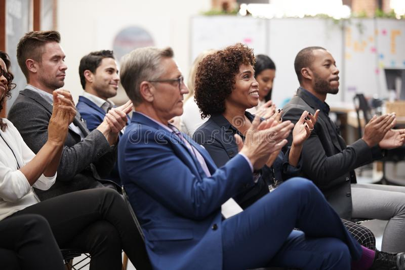 Группа в составе бизнесмены и коммерсантки аплодируя представлению на конференции стоковое фото