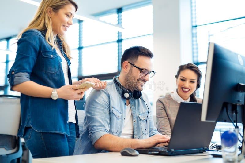 Группа в составе бизнесмены и разработчики программного обеспечения работая в команде в офисе стоковая фотография rf