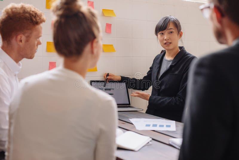 Группа в составе бизнесмены обсуждая данные на компьтер-книжке на встрече стоковое изображение