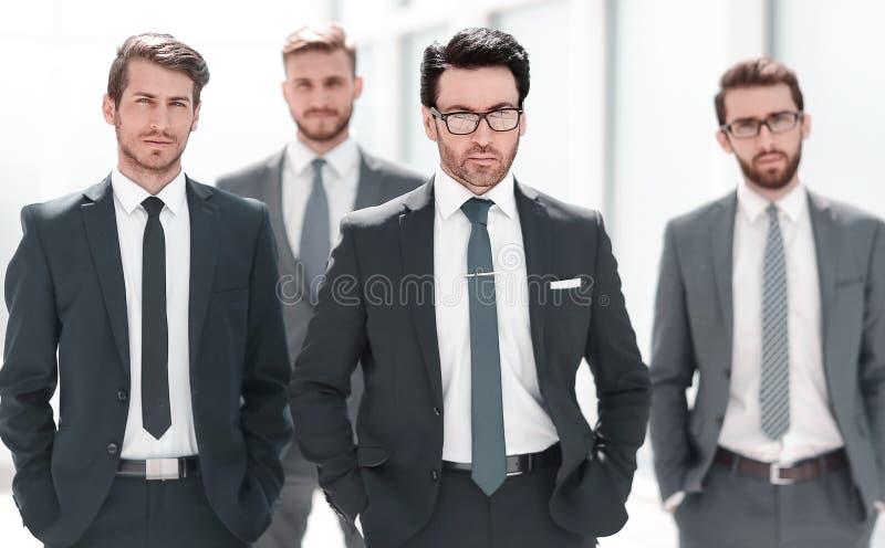 Группа в составе бизнесмены стоя в офисе стоковые изображения