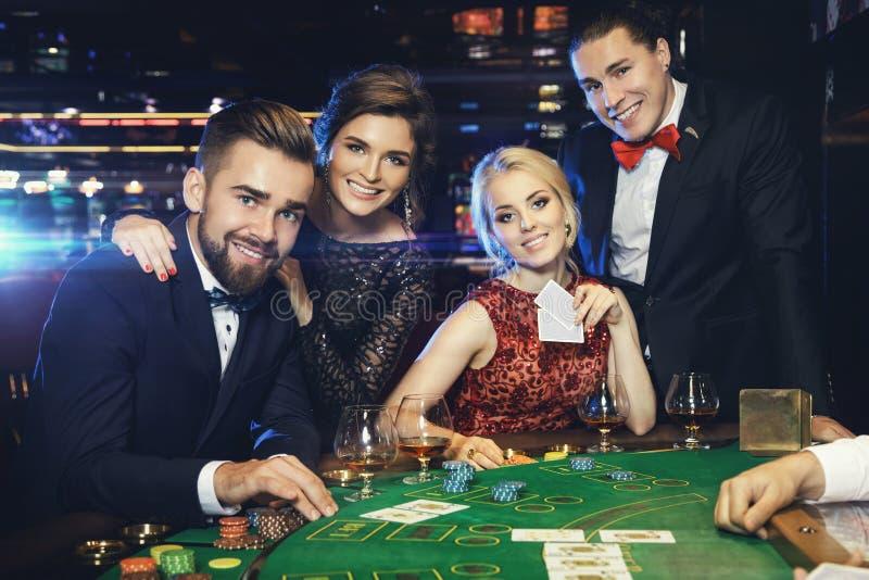 Группа в составе богатые человеки играет покер в казино стоковая фотография