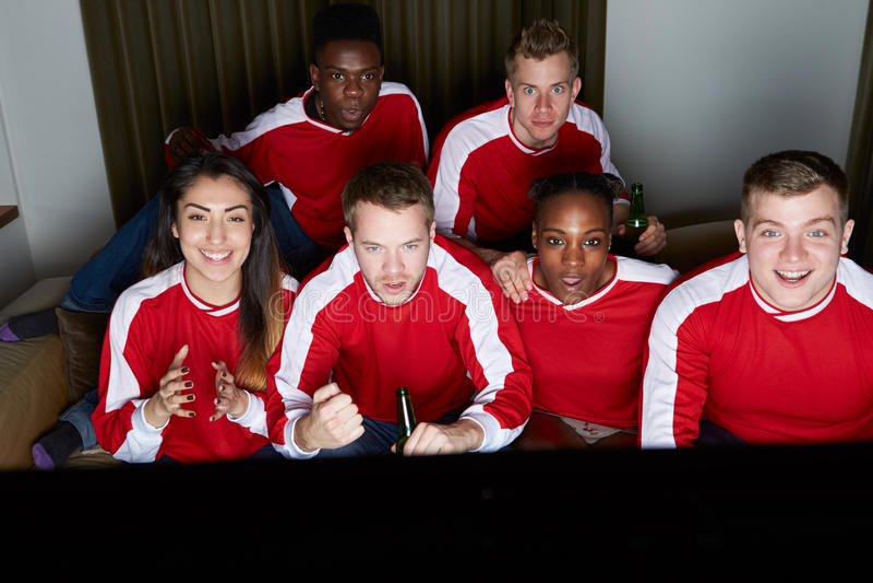 Группа в составе вентиляторы спорт смотря игру на ТВ дома стоковые изображения rf