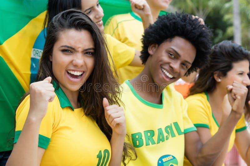 Группа в составе веселить бразильские поклонников футбола с флагом Бразилии стоковая фотография