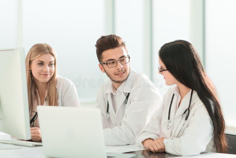 Группа в составе врач-специалисты обсуждая информацию онлайн стоковое фото