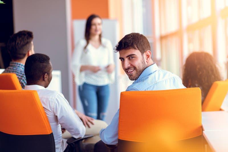 Группа в составе вскользь одетые предприниматели обсуждая идеи в офисе стоковая фотография rf