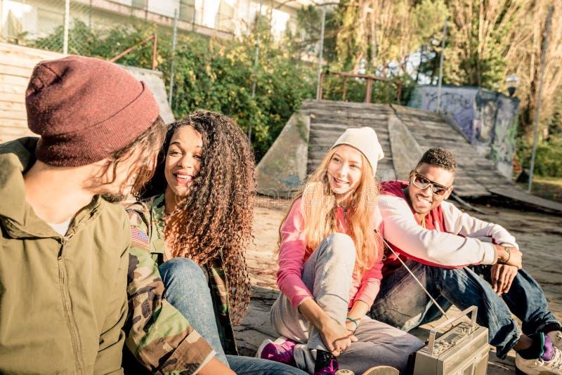 Группа в составе городские друзья имея потеху вне на парке bmx конька стоковое изображение rf