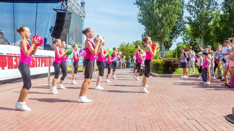 Группа в составе девушки принималась за гимнастику с шариком на фестивале города физической культуры в летнем дне парка солнечном стоковая фотография rf